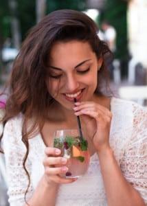 Brunette Woman Sipping Fruit Water Has Nice Teeth