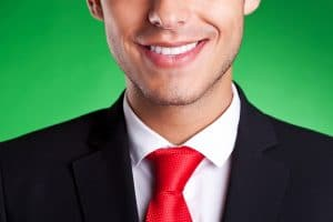 cropped image of a young business man smiling, over green background