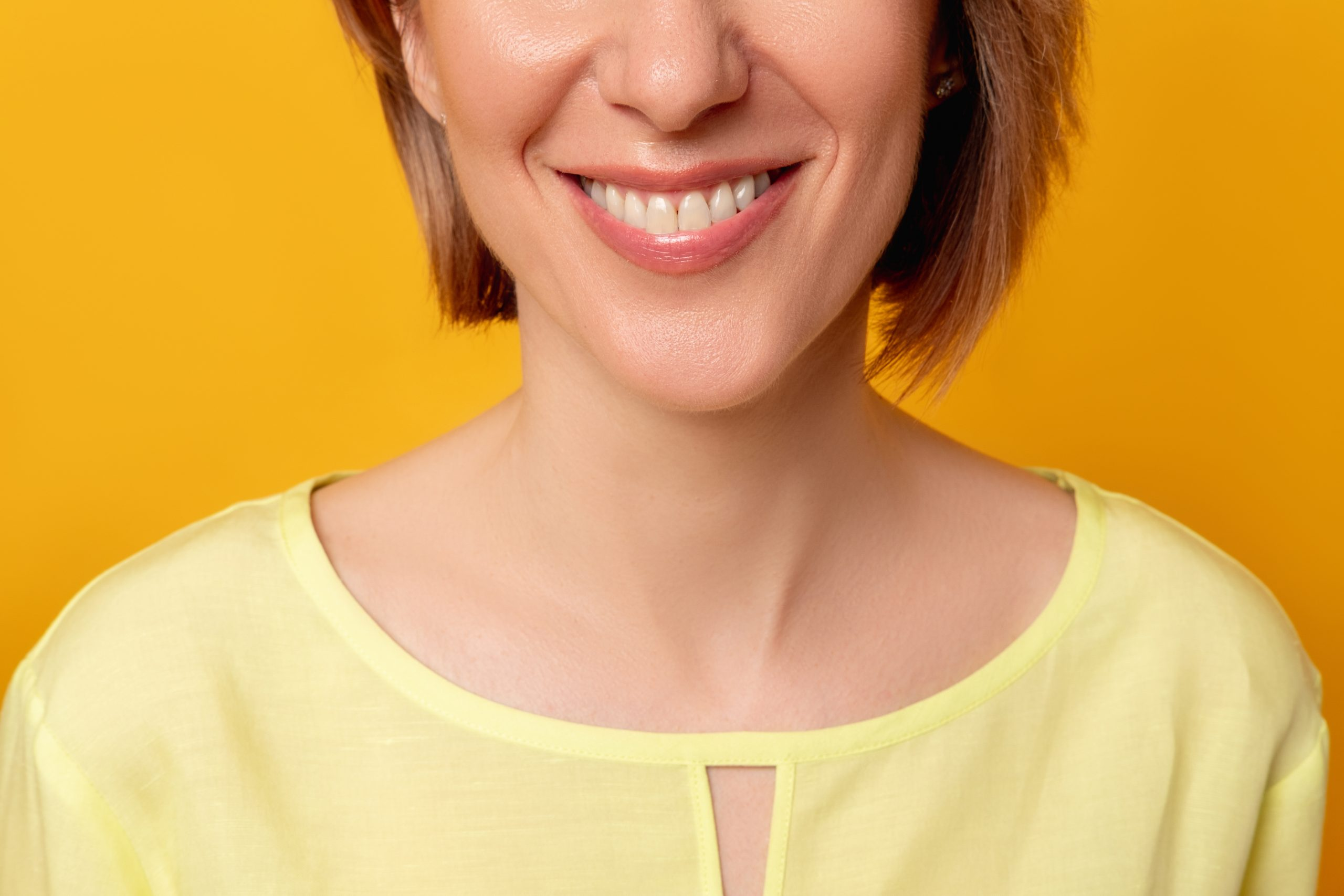 Toothy smile. Dental health. Lip augmentation. Female beauty wellness. Cropped portrait of happy mature woman face with positive emotion isolated on orange background.